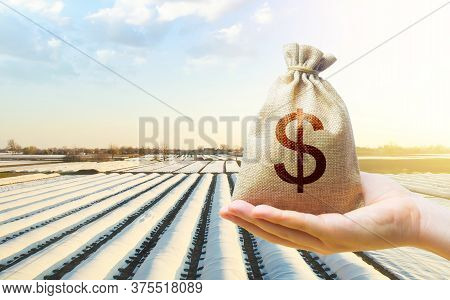 A Hand Holds Out A Dollar Money Bag On A Background Of White Spunbond Agrofibre Rows On A Farm Field