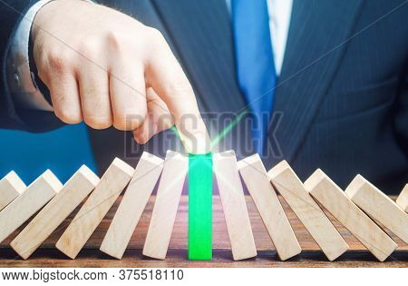 Businessman Stops Process Of Falling Dominoes. Business Systems Processes Recovery. Persistence Stre