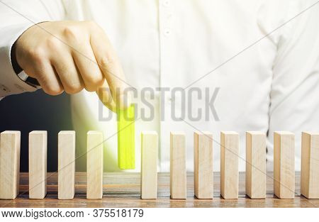 A Man Puts Green Dominoes In A Row. Business Management And Processes. Correct Errors, Make Improvem