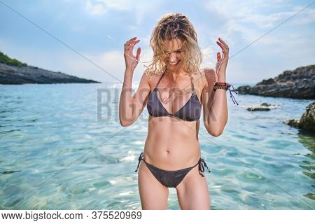 Beautiful african american  woman bathing in the sea on a sunny summer holiday, wet hair, coastal exterior. Adolescent travel lifestyle enjoying the clear sea beach.
