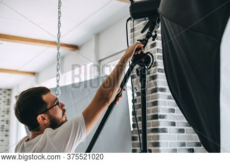 Young Caucasian Man Adjusts Lighting Equipment In A Photo Studio. High Quality Photo