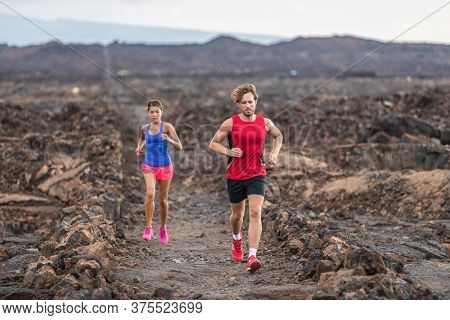 Run couple fit athletes training together running in volcanic trail field for marathon race. Male and female runners in sportswear clothes running shoes.
