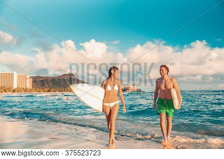 Hawaii Honolulu couple surfers happy on waikiki beach with surfboards. Healthy active sport lifestyle fitness people at sunset with diamond head mountain landscape.