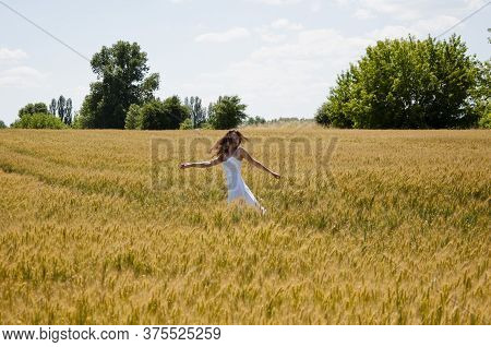 Bohemian Style Of Clothing. Girl Dancing In A Field In A Beautiful White Dress At Sunset. Beautiful