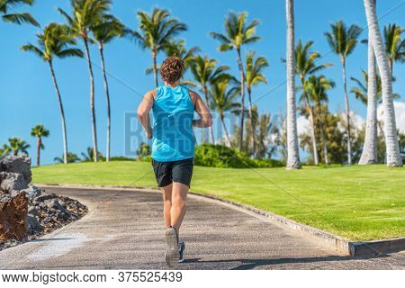 Fit man runner running outdoor on city boardwalk with palm trees background. Young athlete run training fitness jogging in summer sun. Healthy active Florida or Hawaii lifestyle.