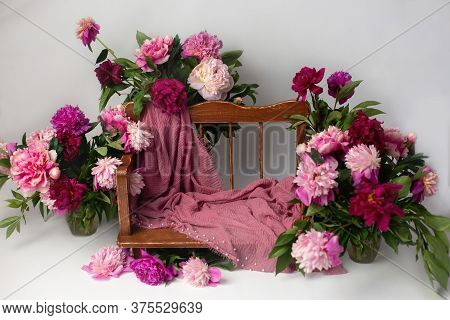 Photo Zone With Props For A Photo Shoot With Flowers. Wooden Bench In Pink Peonies.