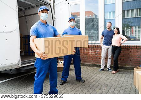 Blue Delivery Men Unloading Package From Truck With Face Mask
