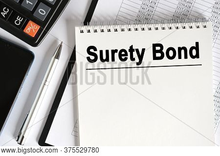 On The Table Lies A Smartphone, A Calculator And A Notebook With The Inscription- Surety Bond. Busin