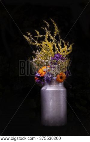 Bouquet With Calendula, Mallow And Field Grass, Bunch In Rustical Milk Churn With Black Background.