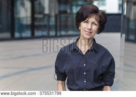 Happy Positive Mature Adult Businesswoman Standing Outdoors Business Centre Smiling, Looking At Came
