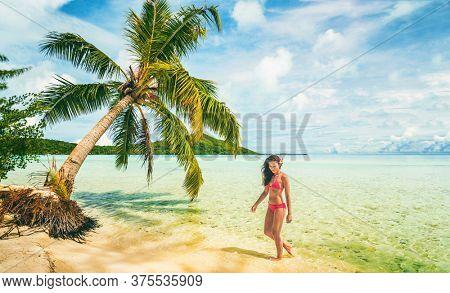 Luxury beach vacation Tahiti Bora Bora bikini woman swimming in paradise getaway destination. Beautiful Asian swimsuit model relaxing .
