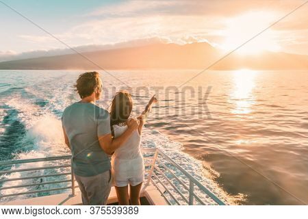 Cruise ship vacation travel tourists couple watching sunset on deck summer travel. lady pointing at sun to man tourist relaxing on Caribbean holidays.