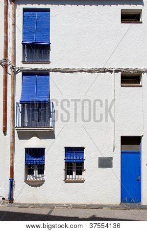 White Facade With Blue Door And Blue Shutters