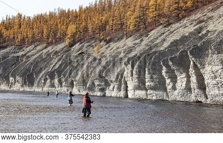 Fishermen Catch Fish With Spinning Rods On The Siberian River. Four Men With Fishing Rods Stand In A