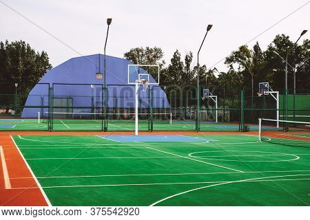Outdoor Sports Field With Artificial Turf For Playing Tennis And Basketball. High Quality Photo