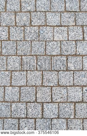 Granite Paving Stones On A Sidewalk Or Pavement Textured Paving Background. Close Up Top View