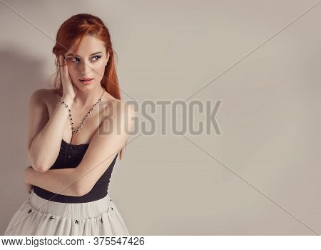 Beauty Woman Portrait With Red Hair. Beautiful Redhead Girl Looking To Side With Hands Touching Face