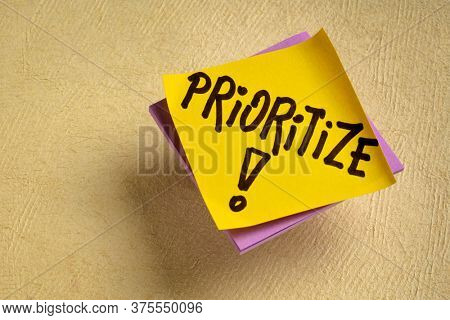 prioritize advice or reminder - handwriting on a sticky note, personal life or business productivity and efficiency concept