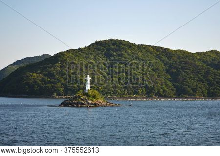 A White Lighthouse Is On A Small Rocky Outcrop, With Trees At Its Base. Small Markers Are Around The