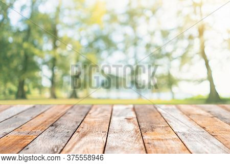 Blur Park And Green Nature Bokeh Leaf  With Sun Light On Copy Space Empty Old Wood Table Abstract Ba