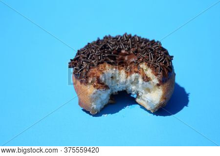 Donut. Cake Donut with Chocolate Frosting and Chocolate Sprinkles. Donut with a bite taken out on blue background.