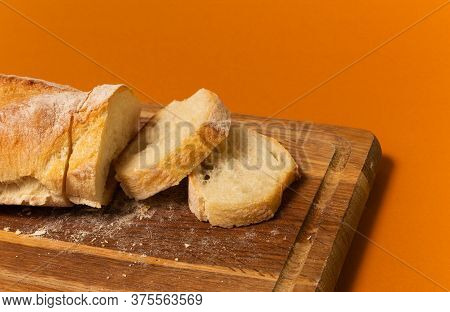Sliced Bread Baguette On A Wooden Cutting Board On A Terracote Color Background. Close Up High Quali