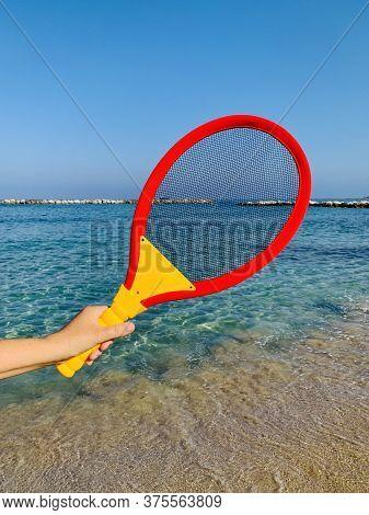 Beach Tennis Racquet In Female Hand On Sandy Beach
