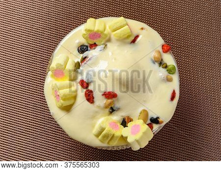 Top View Bowl Of Melting Vanilla Flavor Ice Cream Sundae With Marshmallows And Various Nuts