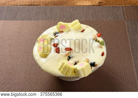 Melted Bowl Of Vanilla Flavor Ice Cream Sundae In A Melting Process With Marshmallows And Various Nu