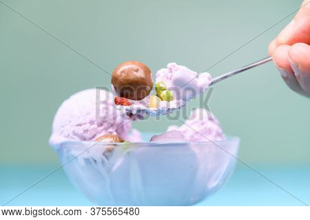 Eating Bowl Of Fresh Sweet Potato Flavor Ice Cream Sundae Mixed With Chocolate Candy And Various Dri