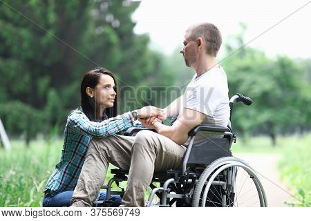 Disabled Male Veteran Is Sitting In Wheelchair Woman Is Sitting Nearby. Difficulties In Relationship