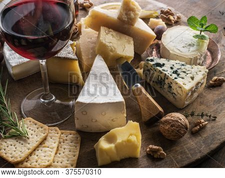 Cheese platter with organic cheeses, fruits, nuts and wine. Tasty cheese starter.