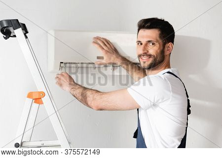 Happy Workman Smiling At Camera While Repairing Air Conditioner