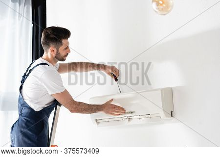 Young Workman Standing On Stepladder And Repairing Air Conditioner With Screwdriver