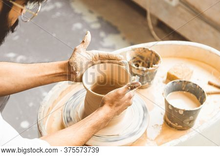 A Young Male Potter Is Engaged In Craft In His Workshop On A Potters Wheel And Makes A Clay Product
