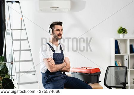Workman In Wireless Headphones Sitting On Desk With Crossed Arms Near Toolbox And Air Conditioner On