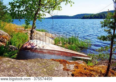 Inverted Old Metal Boat Dries Ashore Lake At Sunny Day. Ladoga Lake Landscape. Overturned Fishing Bo