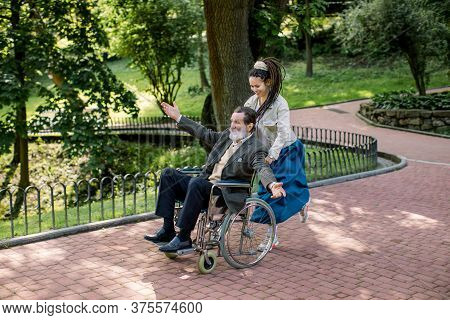 Care Helper Woman, Pretty Young Hipster Granddaughter Walking With Happy Elderly Disabled Man With A