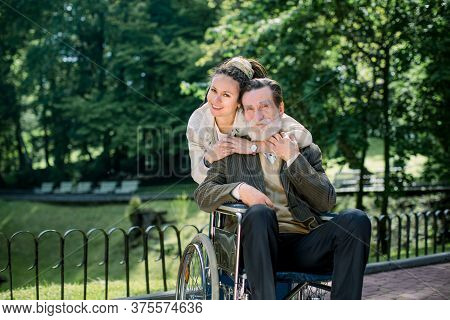 Happy Bearded Senior Man In Wheelchair With Charming Young Girl Supporting Disabled Grandparent On W