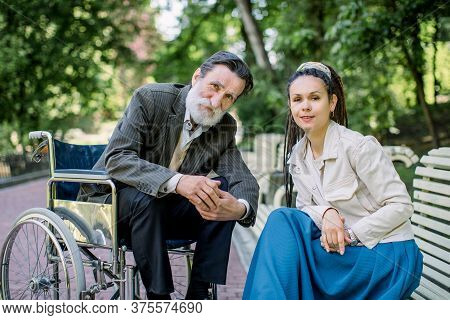 Hipster Female Social Worker And Old Bearded Disabled Man In Wheelchair On A Walk In Park. Caring Nu