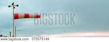 Wind Index Against Cloudy Cloudy Skies. Strong Winds, Storms, Climate Change Concept. Banner. Horizo