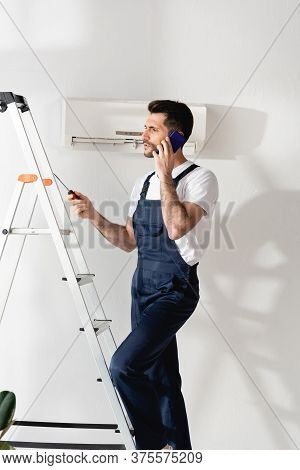 Workman Talking On Smartphone And Holding Screwdriver On Stepladder Near Air Conditioner