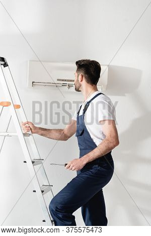 Workman Holding Screwdriver While Standing On Stepladder Near Air Conditioner