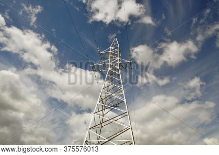 Power Line Mast Against The Blue Sky.