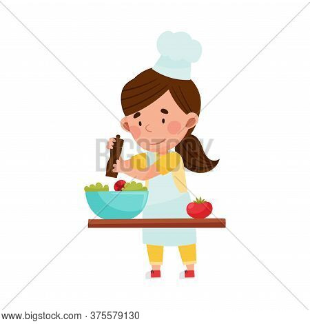 Cute Girl Character In Hat And Apron Standing At Kitchen Table And Dressing Salad Vector Illustratio