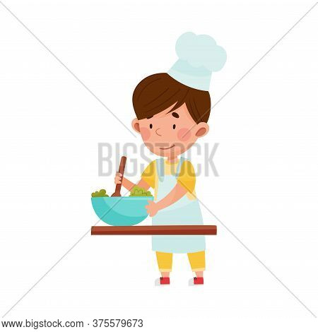Cute Boy Character In Hat And Apron Standing At Kitchen Table And Stirring Salad Vector Illustration