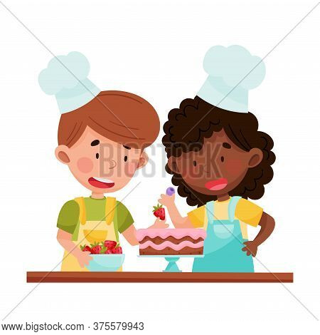 Cute Girl And Boy Chef Characters Wearing Apron And Hat Decorating Cake With Strawberry Vector Illus