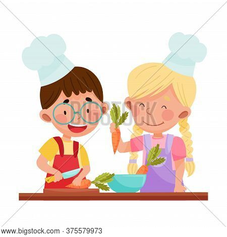 Cheerful Girl And Boy Chef Characters Wearing Apron And Hat Chopping Carrot On Cutting Board Vector