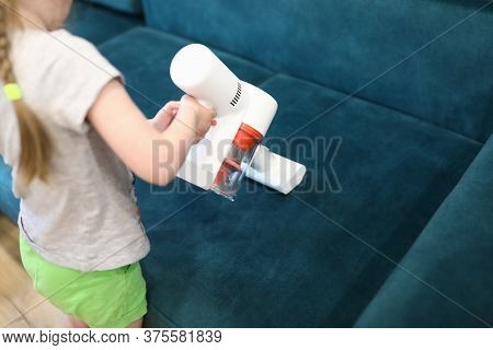 Girl Vacuuming Sofa With Wireless Vacuum Cleaner. Services Cleaning Concept