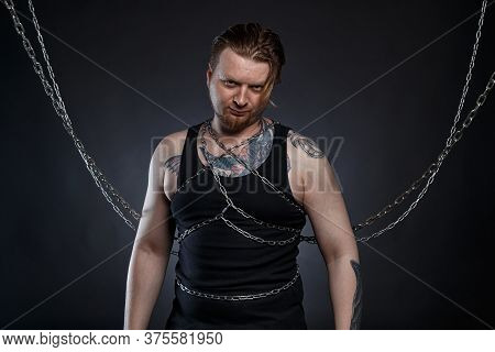 Photo Of A Tattooed Bearded Man Bound In Chains
